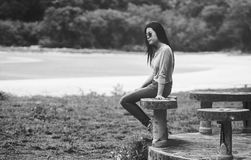 年轻亚裔的妇女戴sunglass坐大理石椅子在海滩附近,黑白,哀伤的概念,选择聚焦 免版税图库摄影