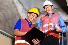 亚裔监督员和工作者建筑工地的 免版税库存图片