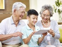 亚裔盛大父母和在家使用片剂的盛大孩子 免版税库存照片