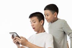 亚裔看在他的片剂的少年和他的兄弟惊奇 库存图片