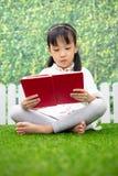 亚裔矮小的中国女孩坐草和阅读书 免版税库存图片