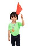 亚裔矮小的中国女孩微笑与旗子和金牌 免版税库存照片