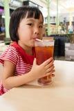 亚裔矮小的中国女孩饮用的冰茶 库存照片