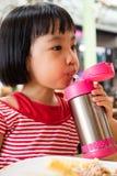 亚裔矮小的中国从不锈钢Bo的女孩饮用水 库存图片