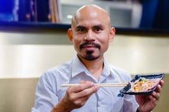 亚裔秃头人有髭使用筷子砍与鱼獐鹿的烤Wagyu牛肉在黑色的盘子的寿司和Tobiko 免版税库存照片