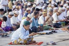 亚裔穆斯林在领域祈祷 图库摄影