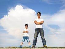 亚裔站立在一个石平台的父亲和儿子 免版税库存照片