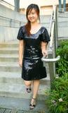 亚裔美丽的下来女孩微笑的台阶走 免版税库存图片