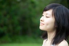 亚裔美丽的享用的女孩户外 免版税库存照片