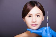 亚裔美丽的妇女得到在她的面孔的射入 审美medi 免版税库存图片