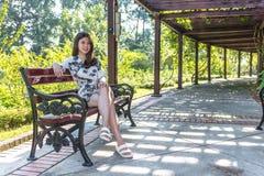 亚裔美丽的少妇坐长凳在室外庭院里 免版税库存图片