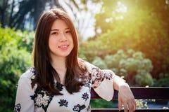 亚裔美丽的少妇坐长凳在室外庭院里 库存图片