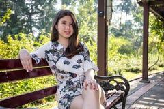 亚裔美丽的少妇坐长凳在室外庭院里 免版税库存照片