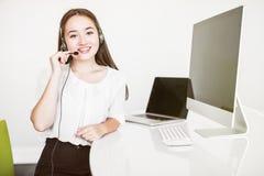 亚裔美丽的微笑的妇女用户支持电话操作员画象在办公室空间背景中 概念电话中心工作 库存图片