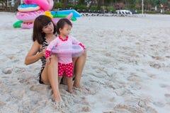 亚裔美丽的母亲投入了婴孩的救生圈 库存照片