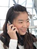 亚裔美丽的移动电话联系的妇女 免版税库存照片