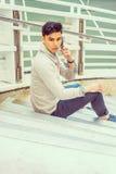 年轻亚裔美国人人谈话在手机外面在新的Yo 库存照片