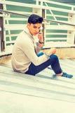 年轻亚裔美国人人谈话在手机外面在新的Yo 免版税库存图片