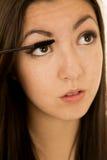 亚裔美国人应用她的染睫毛油的秀丽青少年的gilr 免版税库存照片