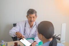 亚裔老人医生谈话与女性患者在医生办公室 免版税图库摄影