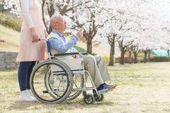 亚裔老人坐有照料者指向的一个轮椅 图库摄影