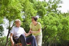 亚裔老人坐有他的妻子的一个轮椅 免版税库存图片