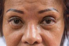 亚裔老妇人显示她眼睛和眼眉纹身花刺 免版税库存照片