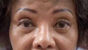 亚裔老妇人显示她眼睛和眼眉纹身花刺 库存图片