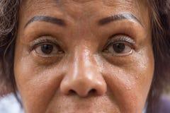 亚裔老妇人显示她眼睛和眼眉纹身花刺 免版税库存图片
