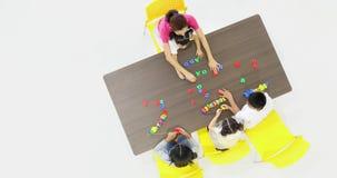 亚裔老师一起演奏有亚裔学生的五颜六色的字母表玩具,教室的概念 股票录像