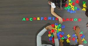 亚裔老师平的被放置的场面录影一起演奏有亚裔学生的五颜六色的字母表玩具, 股票视频