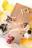 亚裔老师平的被放置的射击演奏五颜六色的修造块一起戏弄与亚裔学生,教室的概念 图库摄影