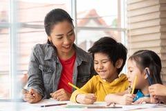 亚裔老师教的艺术和上色与小孩 免版税库存照片