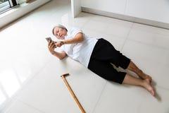 亚裔老年人用拐棍和使用电话要求帮助,有头疼的,说谎在的腰疼病的资深妇女 库存照片