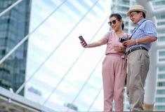亚裔老男人和妇女游人夫妇是行动selfie在大城市中大厦的照片捕获  也这张照片 免版税库存图片
