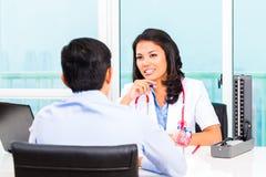 亚裔耐心咨询医生的办公室 图库摄影