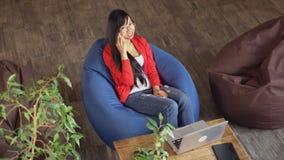 亚裔职业妇女谈话在坐在颜色椅子鞋帮视图的智能手机 影视素材
