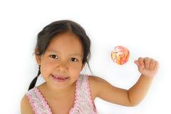 亚裔被中断的牙女孩和大lollypop 免版税图库摄影