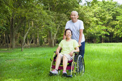 亚裔资深妇女坐有他的丈夫的一个轮椅 库存图片