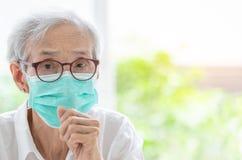 亚裔资深妇女遭受与面膜保护,年长由于空气污染,老病残的妇女佩带的面膜的咳嗽 库存图片