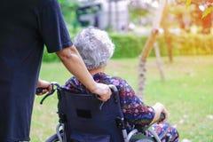 亚裔资深或年长老妇人妇女患者,小心帮助和支持在轮椅在公园 图库摄影
