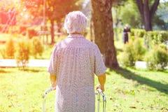亚裔资深或年长老妇人妇女用途步行者以强的健康在公园 免版税库存图片