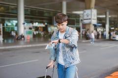 亚裔迷茫的男性游人看他的手表机场 库存图片
