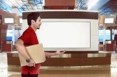 亚裔送货人侧视图送一个小包 免版税库存图片