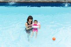 亚裔逗人喜爱的使用在水池的孩子女孩和母亲 图库摄影
