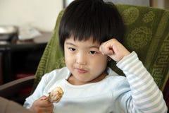 亚裔逗人喜爱的吃的女孩少许 库存图片