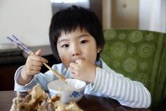亚裔逗人喜爱的吃的女孩少许 免版税库存图片