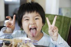 亚裔逗人喜爱的吃的女孩少许 免版税库存照片