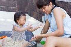 亚裔逗人喜爱的女婴和母亲喜欢演奏沙子 库存照片