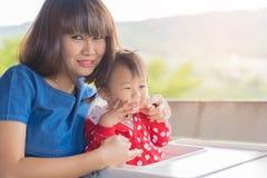 亚裔逗人喜爱的女婴和美丽的母亲enjoyful在山b 库存照片